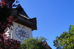 Grazer Uhrturm. Clocktower in the light of the setting sun from park Schlossberg Stock Photos