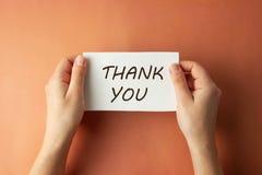 Grazie iscrizione La donna che tiene la carta con vi ringrazia che segnate nel fondo marrone isolato mani Vista superiore fotografia stock