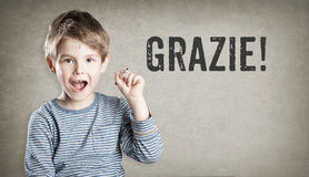 Grazie! Italian thanks, Boy on grunge background writing Royalty Free Stock Photography