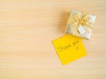 Grazie parole sulla nota appiccicosa con il contenitore di regalo Fotografia Stock