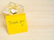 Grazie parole sulla nota appiccicosa con il contenitore di regalo dell'oro su backgr di legno Immagine Stock