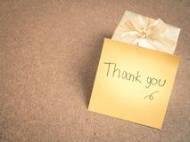 Grazie parole sulla nota appiccicosa con il contenitore di regalo dell'oro su backgr di legno Fotografie Stock