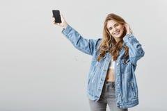 Grazie pieni di energia alle grandi canzoni Ritratto della donna attraente felice positiva in rivestimento alla moda del denim ch Fotografie Stock Libere da Diritti