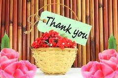 Grazie segnare l'etichetta o l'etichetta con lettere con il canestro del bambù e del fiore Immagine Stock