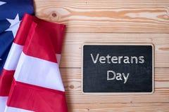 Grazie testo dei veterani scritto in lavagna con la bandiera degli Stati Uniti d'America su fondo di legno immagine stock