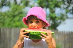 Gready girl eating a fresh watermelon slice Stock Image