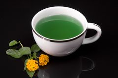 Grean Tea. On black background with yellow flowers Stock Image