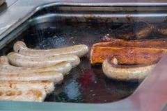 Grease covered grill with bratwurst and hamburgers cooking royalty free stock photography