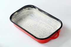 Greased baking tin covered with coconut Stock Photos