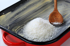 Greased baking tin with desiccated coconut Royalty Free Stock Photos