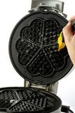 Greasing waffle iron with brush, close-up Royalty Free Stock Images