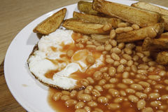Greasy cafe meal of egg beans and chips. Poorly presented food. Greasy cafe meal of fried egg, baked beans and chips. Poorly presented fast food Stock Photography