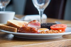 English cooked fried breakfast, 6 items and toast. A greasy fried breakfast of sausage, black pudding, bacon, beans, egg, tomato and toast royalty free stock photo