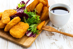 Greasy fried chicken, french fries, ketchup and salad. Stock Photography