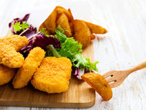 Greasy fried chicken, french fries, ketchup and salad. Stock Image