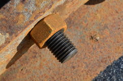 Greasy screw with rusty nut at a steel pipe Royalty Free Stock Image