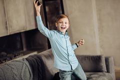 Happy pre-teen boy celebrating victory in game. Great achievement. Upbeat pre-teen boy kneeling on the sofa and raising his hands in a gesture of triumph, having Royalty Free Stock Images
