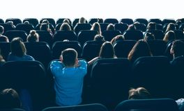 People watching movie in cinema hall. Great ammount of people watching movie in big cinema hall, sitting on comfortable places. Backview of women, men and royalty free stock photo