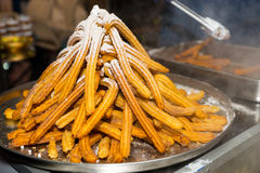 A great amount of confectionery product Churros. With powdered sugar at food festival stock image