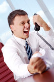 Great anger. Image of annoyed boss losing his temper and screaming into phone receiver Stock Photography