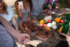 Great appetizing sausages, grilled. Friends eat fried sausages outdoors. Summer vacation with friends. Stock Image
