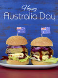 The Great Aussie BBQ Burger with Australia Day sample text. The Great Aussie BBQ Burger - with barbeque beef burgers and salad piled high with Australian flag Royalty Free Stock Image