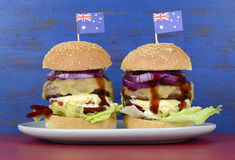 The Great Aussie BBQ Burger. With barbeque beef burgers and salad piled high with Australian flag against a red and blue distressed wood background Royalty Free Stock Photo