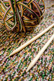 Great ball of colored yarn, wooden knitting needles and fabric Stock Photo