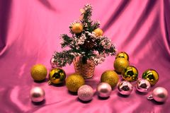 Great beautiful Christmas tree decorated with pink balloons, ribbons, snowflakes and toys under them. Great beautiful Christmas tree decorated with pink Stock Images