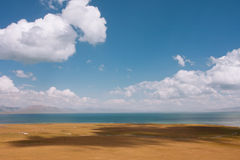 Great blue lake under white clouds. Panorama with lake and blue cloudy sky above Royalty Free Stock Photography