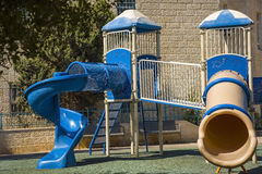 Great blue slide in a children's playground,  modern example of how kids can play safe and have  lot  fun. Royalty Free Stock Images