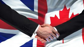 Great Britain and Canada handshake, international friendship, flag background. Stock footage stock video footage