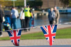 Great Britain celebration bunting with typical UK background in. UK Warwickshire bright union jack flag triangle bunting with typical British background Royalty Free Stock Image