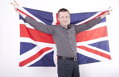 Great Britain fan. Man holding flag of Great Britain with both hands and showing victory sign Royalty Free Stock Images