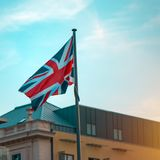 Great Britain flag on the pole. In sunset Royalty Free Stock Images