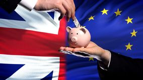 Great Britain investment in EU hand putting money in piggybank, flag background. Stock photo stock photo