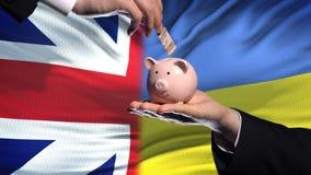 Great Britain investment in Ukraine hand puts money in piggybank flag background. Stock footage stock video footage