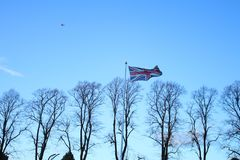 Great Britain`s flag fluttering in the wind. Wallpaper with clear blue sky stock photography