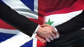 Great Britain and Syria handshake, international friendship, flag background. Stock footage stock video