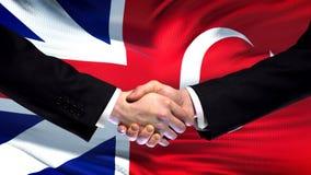 Great Britain and Turkey handshake, international friendship, flag background. Stock photo stock images