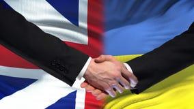 Great Britain and Ukraine handshake, international friendship, flag background. Stock footage stock footage