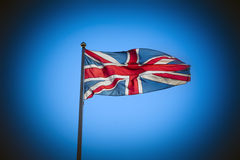 Great Britain Union Jack flag flying against blue sky Royalty Free Stock Photo