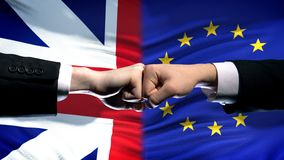 Great Britain vs EU conflict, international relations, fists on flag background. Stock photo stock images