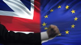 Great Britain vs EU confrontation, interests conflict, fists on flag background. Stock footage stock video