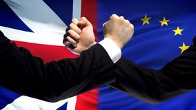 Great Britain vs EU confrontation, interests conflict, fists on flag background. Stock photo royalty free stock photo