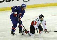 Great Britain vs. Hungary IIHF World Championship ice hockey mat. BUDAPEST - APRIL 14: Hungarian Janos Hari (R) is hooked by British Jonathan Weaver during Great Stock Photos