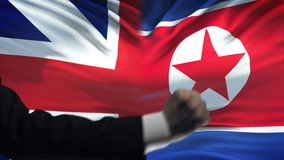 Great Britain vs North Korea confrontation, fists on flag background, diplomacy. Stock footage stock video