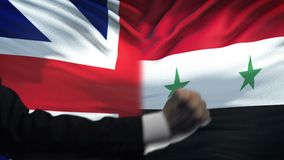 Great Britain vs Syria confrontation, fists on flag background, diplomacy. Stock footage stock video