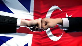 Great Britain vs Turkey conflict, fists on flag background, diplomatic crisis. Stock photo royalty free stock photography