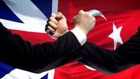 Great Britain vs Turkey confrontation, fists on flag background, diplomacy. Stock photo royalty free stock photo